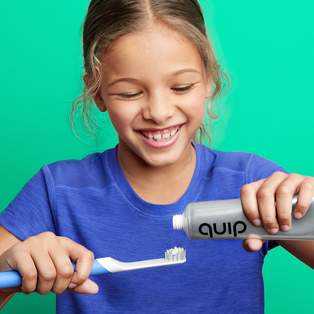 Girl adding toothpaste to brush